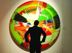 A man observes one of Damien Hirst's spin paintings